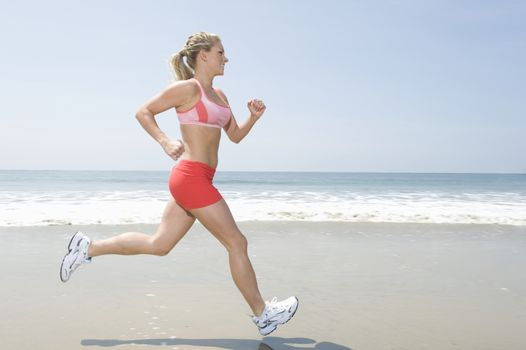 Woman jogging along beach