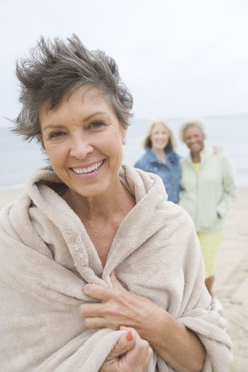 Mature woman stands in towel on beach