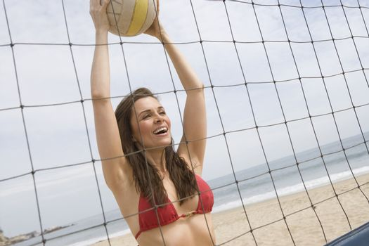 Woman in red bikini at volleyball net