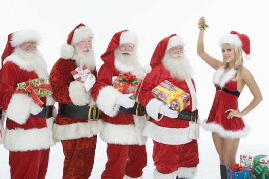 Group of men dressed as Santa Claus Mrs Claus holding mistletoe