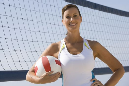 Woman at beach volleyball net with ball