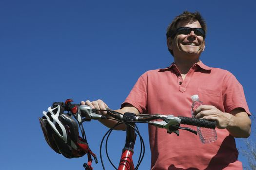 Mature man stands holding bicycle handlebars