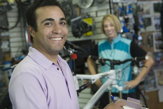 Bike shop assistant with female cyclist