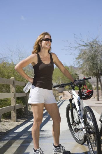 Mature woman stands with bicycle on path