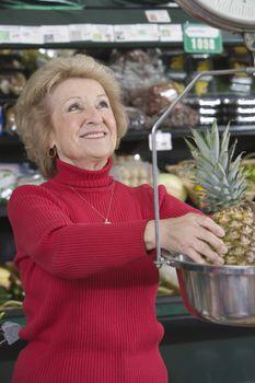 Senior woman weighing pineapple in supermarket