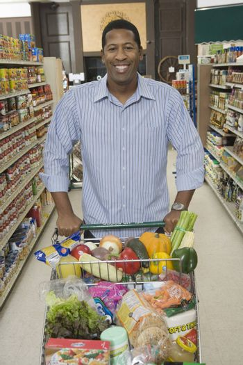 Mature man stands with grocery shopping in supermarket aisle