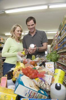 Mature couple look at jar in supermarket aisle
