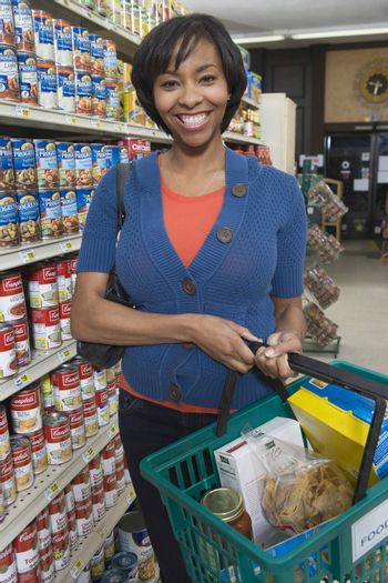 Mature woman stands with grocery shopping in supermarket aisle