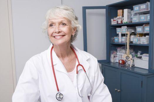 Senior medical practitioner stands at medical cabinet