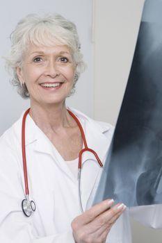 Senior medical practitioner holding xray