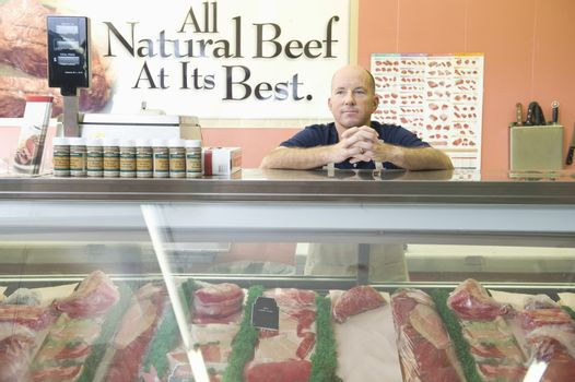 Supermarket employee stands at meat counter in supermarket