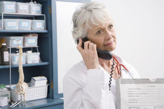 Senior medical practitioner stands on phone at medical cabinet