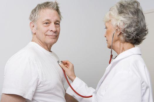 Senior medical practitioner examines man with stethoscope