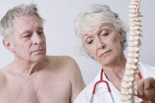 Senior medical practitioner explains anatomical model