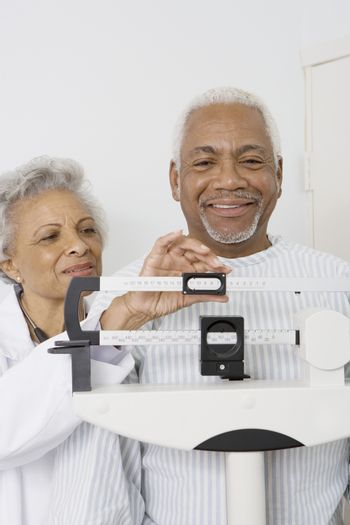 Senior medical practitioner checks weight of patient