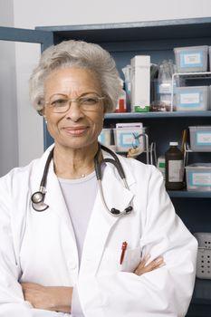 Portrait of senior medical practitioner and medicine cabinet