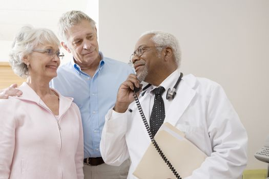 Senior medical practitioner on the phone with a senior couple