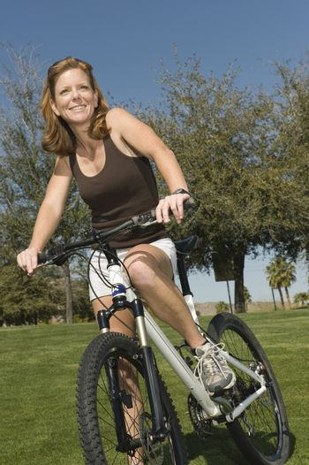 Mature woman stands with mountain bike