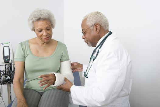 Senior practitioner adjusts plaster cast on broken arm
