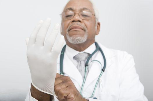 Senior practitioner pulls on surgical gloves