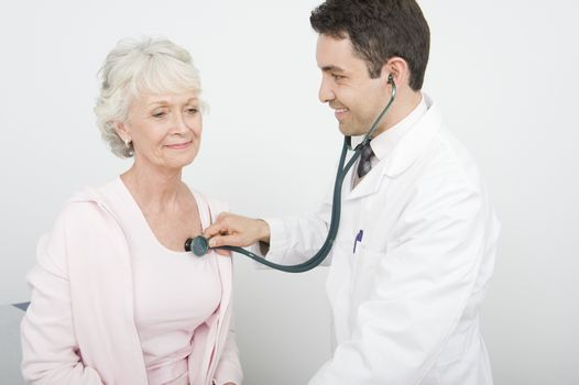 Mid adult doctor checks breathing of senior patient