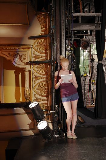 Full length of a young woman reading script backstage