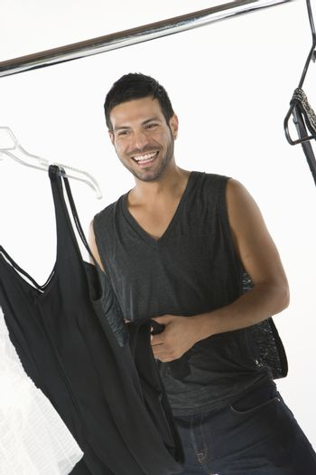 Wardobe stylist stands with clothes rail smiling
