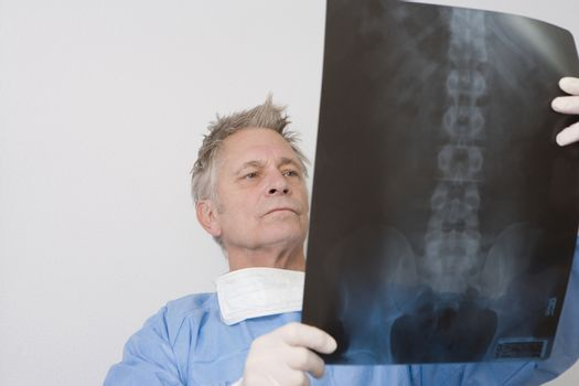 Senior medical practitioner stands with xray