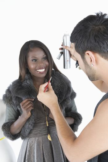 Hair stylist makes adjustments to model in fake fur jacket