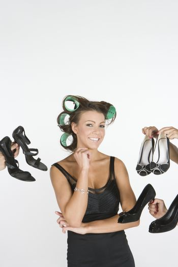 Woman in rollers with a choice of footwear on hand