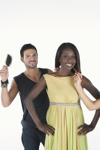 hair stylist stands behind model in yellow dress with hairbrush
