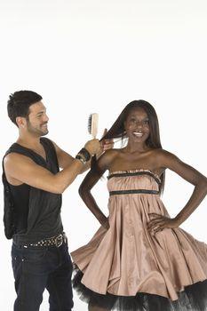 Hair stylist adjusts models hair