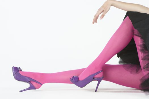 Low section of pink tights and purple high heeled shoes