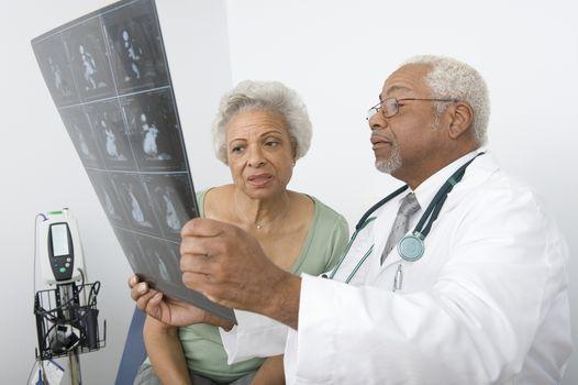 Senior practitioner  and patient examine xray
