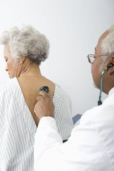Senior practitioner listens to breathing through stethoscope