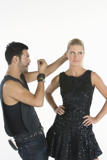 Hair stylist makes adjustments to model standing with hands on hips