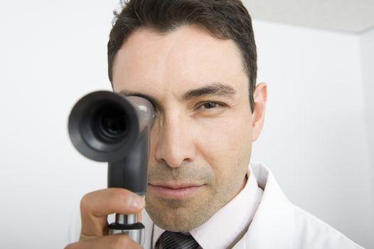 Optician looks through sight testing equipment