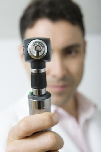 Mid adult doctor looks through sight testing equipment
