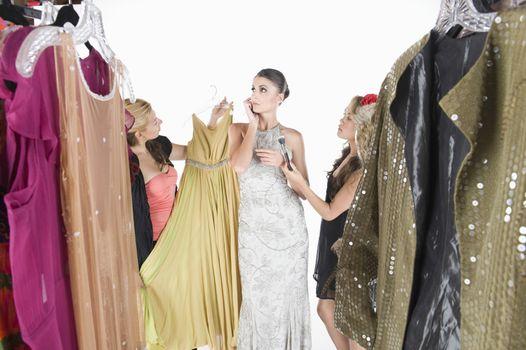 Woman stands ignoring wardrobe assistants