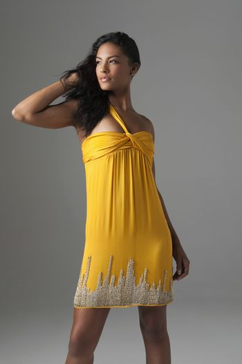 Woman stands in bright yellow dress