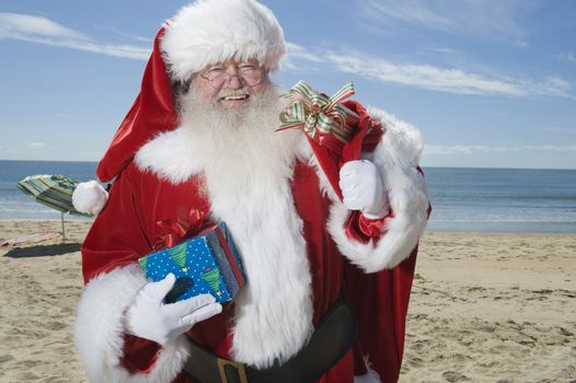 Father Christmas stands with his sack on a beach