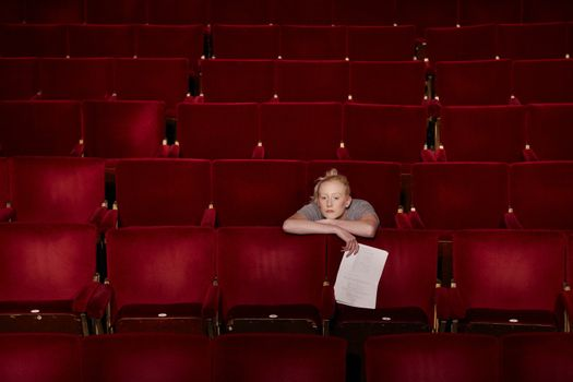 Thoughtful young woman sitting in theatre stall with script