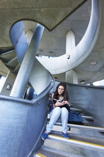 University student reading on staircase