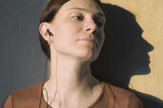 Shadow of redhead listening to headphones