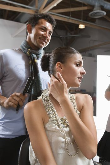 Mid adult woman and hair stylist