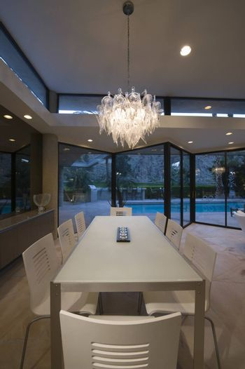 Lit glass chandelier over dining table in modern house