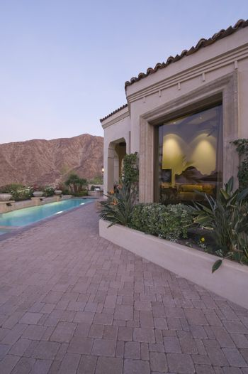 Paved poolside area and window exteriors of Palm Springs home