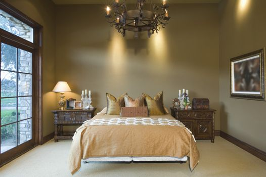 Chandelier hanging over tidy bed at home