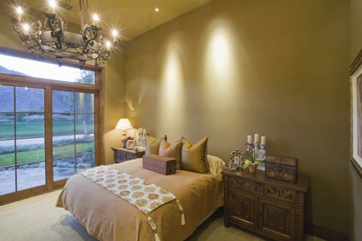 Lit chandelier over bed with view of landscape through window at home