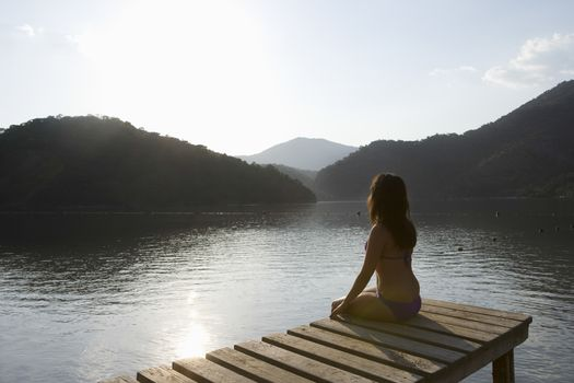 Young woman sits on lakeside jetty at dawn